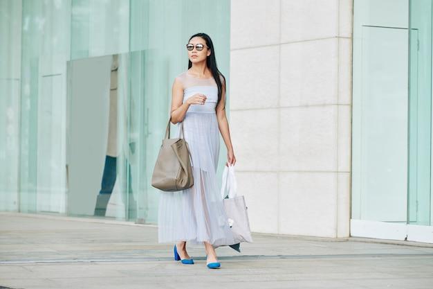 Donna asiatica abbastanza giovane nella mascherina medica con il sacchetto che cammina per strada