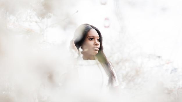 Bella giovane donna di colore in abiti bianchi vicino a fiori bianchi sulla natura nel parco. tenera ragazza di moda africana in abito bianco cammina vicino a un albero in fiore nel giardino. concetto di bellezza naturale