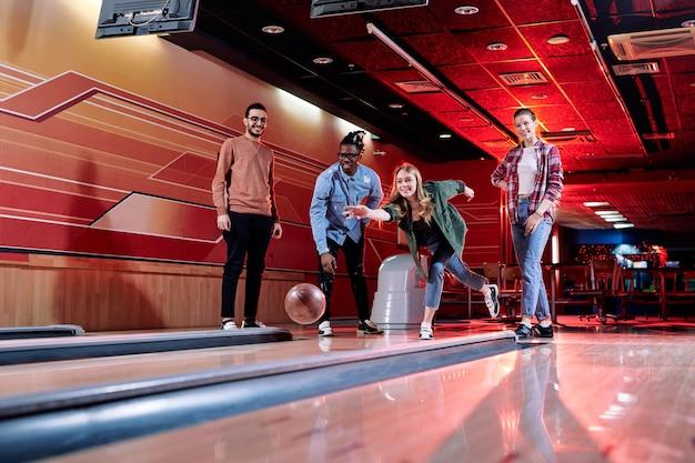 Piuttosto giovane donna bionda che lancia palla da bowling in pista mentre si trovava tra i suoi amici interculturali durante il gioco