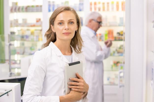 Piuttosto giovane farmacista biondo o operaio della farmacia contemporanea con tavoletta digitale in piedi davanti alla telecamera contro un collega invecchiato