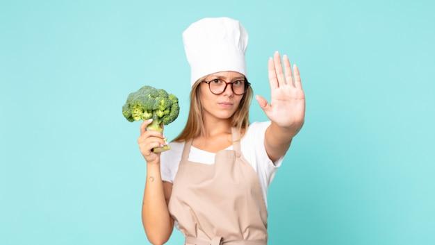 Donna chef bionda abbastanza giovane che tiene un broccolo