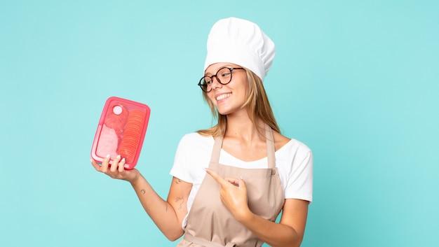 Donna chef bionda abbastanza giovane e con in mano un tupperware