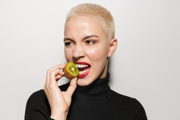 Bella giovane donna bionda alla moda con taglio di capelli corto in posa isolato sul muro bianco che tiene il kiwi.