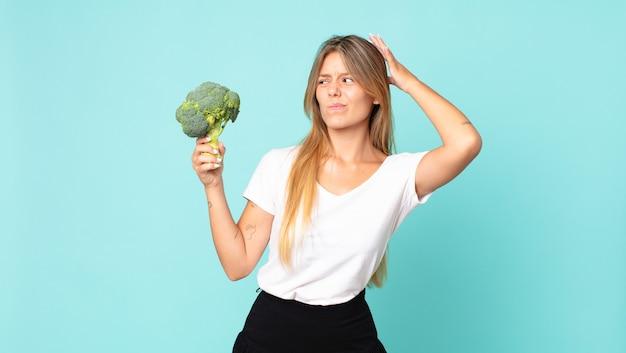 Donna bionda abbastanza giovane che tiene un broccolo