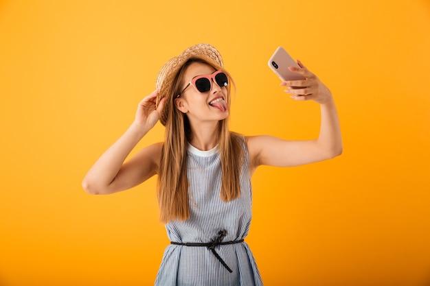 Piuttosto giovane donna bionda in cappello estivo e occhiali da sole