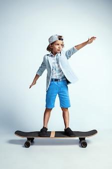 Ragazzo abbastanza giovane su skateboard in abiti casual su bianco