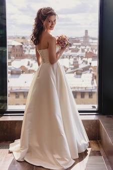 La sposa abbastanza giovane sta alla finestra in hotel con viste stupefacenti della città. mattina della sposa il giorno del matrimonio. il mazzo felice della sposa nelle mani aspetta di incontrare lo sposo. spazio del copyright