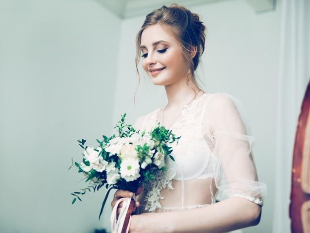 Piuttosto giovane sposa con un bouquet da sposa