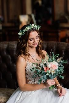 Sposa castana abbastanza giovane in un abito da sposa elegante e acconciatura in hotel in interni di lusso.