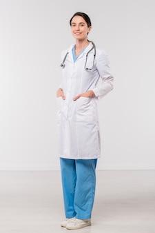 Medico abbastanza giovane del brunette in uniforme medica che tiene le sue mani nelle tasche di whitecoat nell'isolamento