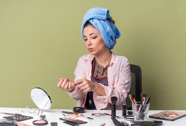 Bella ragazza bruna con i capelli avvolti in un asciugamano seduto al tavolo con strumenti per il trucco che si abbottonano la manica della camicia