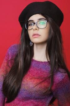 Bruna abbastanza giovane in vestiti alla moda e occhiali che guarda l'obbiettivo mentre levandosi in piedi su sfondo rosso brillante