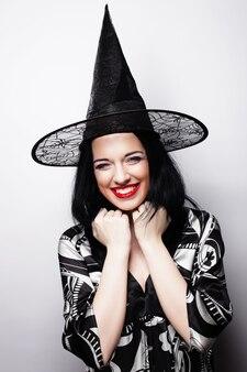Piuttosto giovane strega bruna con cappello nero, isolata su sfondo bianco