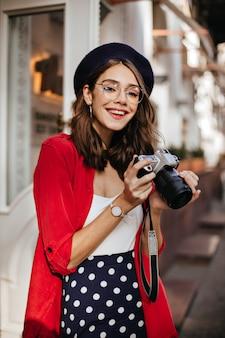 Bella giovane bruna con trucco, berretto e occhiali, indossa un top bianco, una camicia rossa e una gonna a pois, sorride e tiene la macchina fotografica in mano per strada