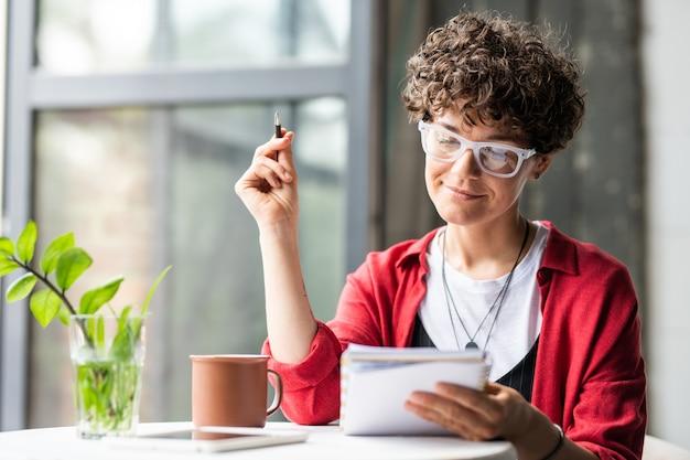 Piuttosto giovane donna bruna guardando attraverso i suoi appunti in taccuino mentre si lavora su un nuovo progetto o si pensa a idee