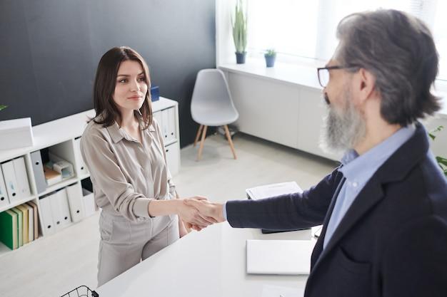 Piuttosto giovane donna bruna in tuta di handshake con professionista sulla scrivania alla riunione dopo essere venuti a patti e firmare documenti