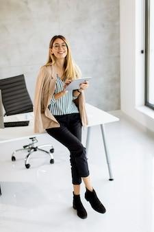 Donna abbastanza giovane di affari che tiene compressa digitale e in piedi nell'ufficio moderno