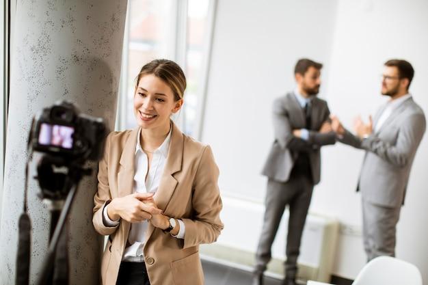Donna d'affari abbastanza giovane che guarda la telecamera mentre giovani uomini d'affari lavorano insieme in ufficio