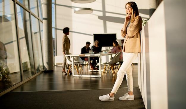 Piuttosto giovane donna d'affari in piedi in ufficio e utilizzando il telefono cellulare di fronte alla sua squadra