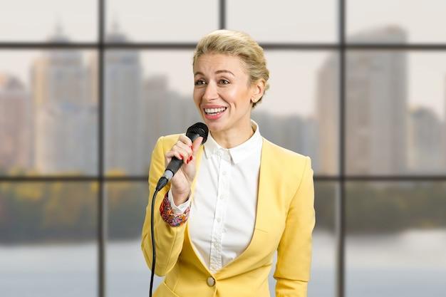Donna di affari abbastanza giovane che dà una presentazione. parlando in pubblico giovane imprenditrice, finestra del business center
