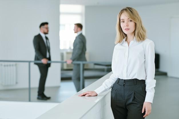 Piuttosto giovane imprenditrice con i capelli biondi in piedi da ringhiere all'interno di un grande ufficio con due uomini d'affari che hanno conversazione