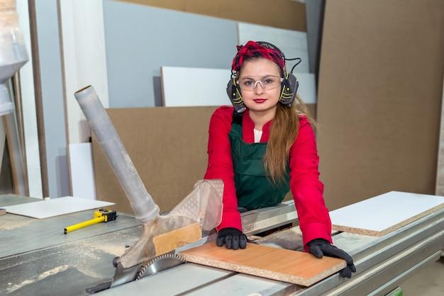Grazioso e giovane operaio di falegnameria che sega la tavola di legno
