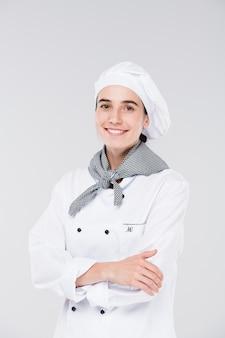 Piuttosto giovane chef in uniforme bianca ti guarda con un sorriso mentre incrocia le braccia dal petto davanti alla telecamera in isolamento