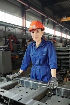 Piuttosto giovane operaio fiducioso in uniforme blu, guanti e casco in posa