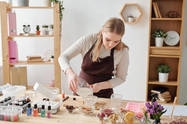 Piuttosto giovane artigiana in grembiule marrone che versa la massa di sapone liquido dalla grande ciotola di vetro in una più piccola