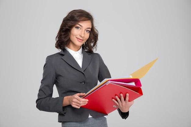 Piuttosto giovane donna d'affari sorridente felice riccia in abito grigio che lavora con cartelle colorate