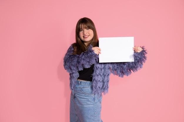 Piuttosto giovane donna dai capelli scuri. contiene un foglio di carta bianco, pulito e bianco per i sorrisi di iscrizione, guarda nella cornice. foto su sfondo rosa in studio.