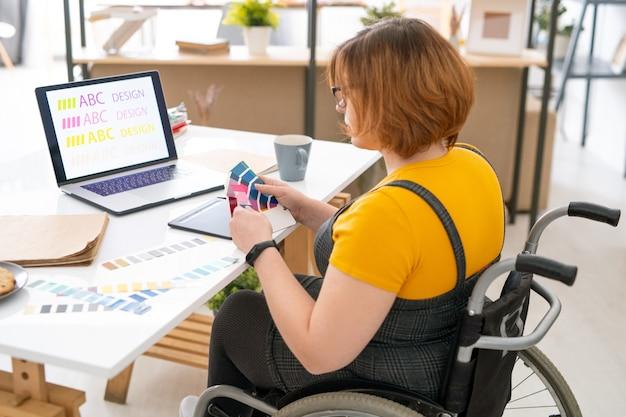 Piuttosto giovane designer di abbigliamento casual seduto sul posto di lavoro in ambiente domestico e scegliendo il colore per il design del sito web dalla tavolozza