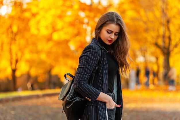 Piuttosto giovane donna d'affari elegante con un abito nero in una giacca con uno zaino in pelle cammina in un parco autunnale con fogliame arancione colorato brillante al tramonto