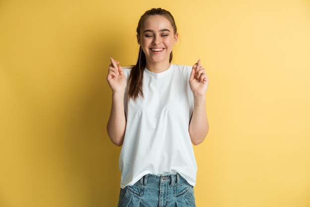Piuttosto giovane donna eccitata in maglietta bianca ha incrociato le dita, esprime un desiderio desiderabile, aspetta buone notizie su uno sfondo giallo.