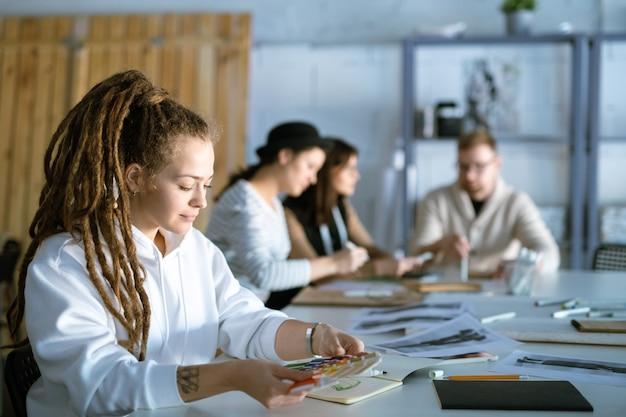 Stilista abbastanza giovane con tavolozza dei colori seduto alla scrivania in studio mentre si lavora sulla nuova collezione stagionale