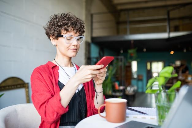 Piuttosto giovane donna o imprenditrice con lo smartphone che cattura foto della tazza di caffè mentre è seduto a tavola nella caffetteria