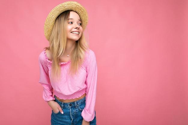 Una donna piuttosto giovane che indossa una camicetta rosa e un cappello estivo beige