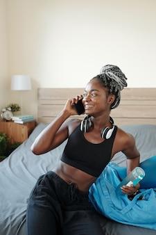 Donna di colore abbastanza giovane in forma con una bottiglia d'acqua che riposa sul letto dopo l'allenamento e parla al telefono con un amico