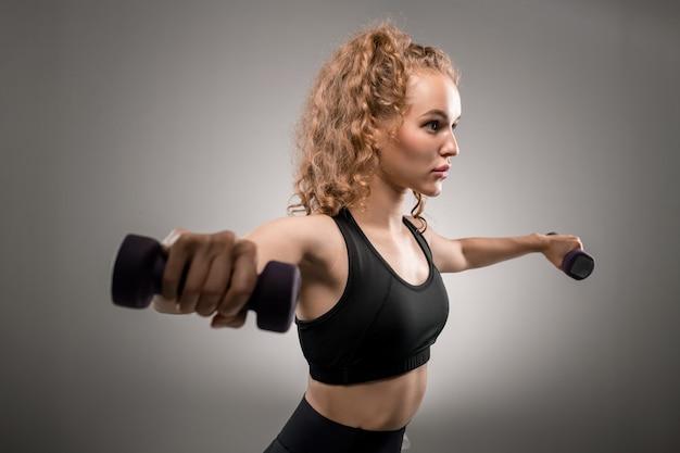 Femmina abbastanza giovane in forma con capelli biondi ricci che allungano le braccia con manubri mentre si esercita al mattino su gray