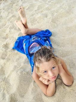 La ragazza graziosa in pareo blu sta trovandosi sulla spiaggia e sta cercando.