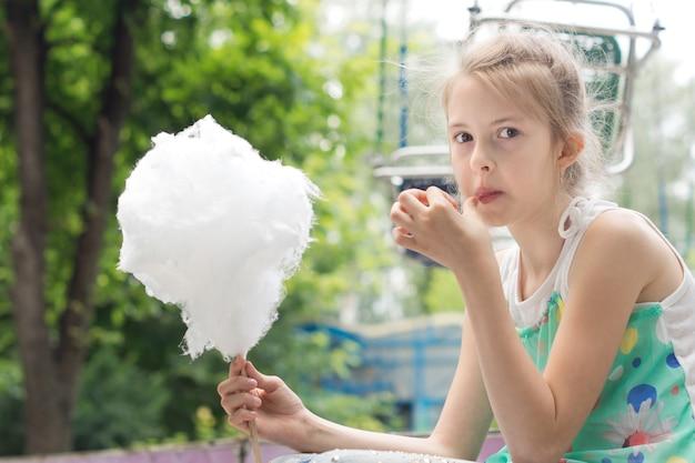 Ragazza graziosa che mangia un bastoncino di zucchero filato