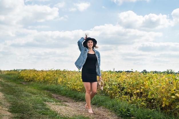 La ragazza graziosa gode delle vacanze estive che camminano al campo rurale