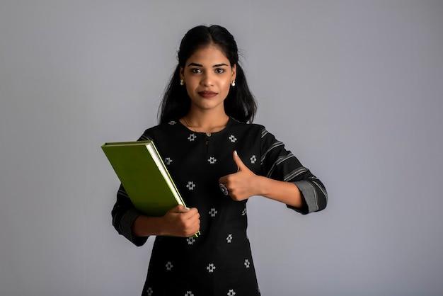 Ragazza graziosa che tiene libro e posa su sfondo grigio