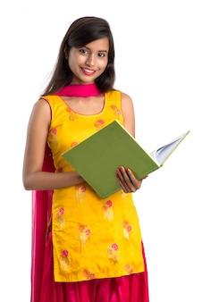 Libro grazioso della tenuta della ragazza e posare sulla superficie bianca