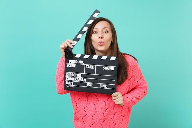 La ragazza graziosa in maglione rosa lavorato a maglia che soffia l'invio di baci d'aria tiene in mano il classico film nero che fa il ciak isolato sul fondo della parete blu. concetto di stile di vita della gente. mock up copia spazio.