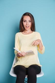 Bella ragazza che punta il dito sul libro e si siede su una sedia su sfondo blu