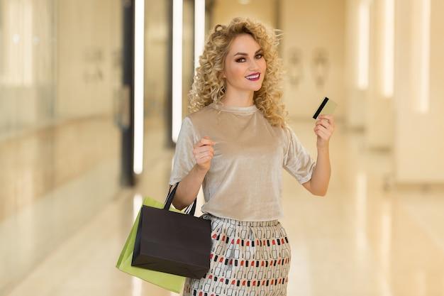 Ragazza graziosa che mostra la carta di credito nel centro commerciale