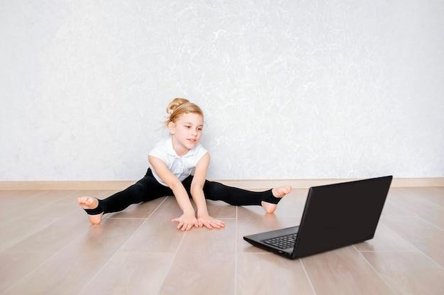 La ragazza graziosa in abiti sportivi che guarda il video online sul computer portatile e che fa la forma fisica si esercita a casa. formazione a distanza con personal trainer, distanza sociale o autoisolamento, concetto di formazione online