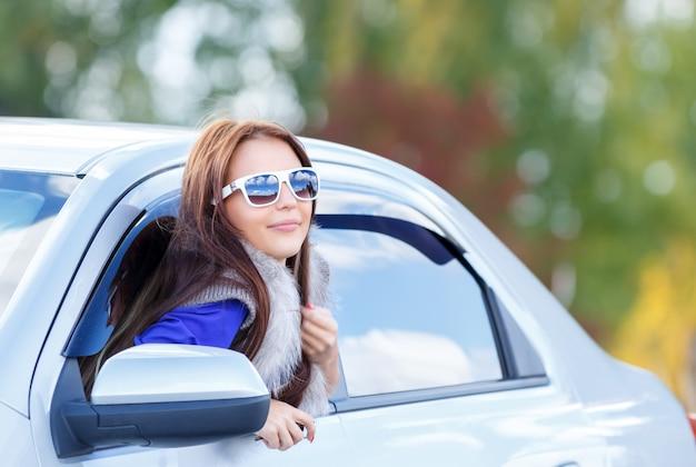 Ragazza graziosa in occhiali da sole all'interno dell'auto
