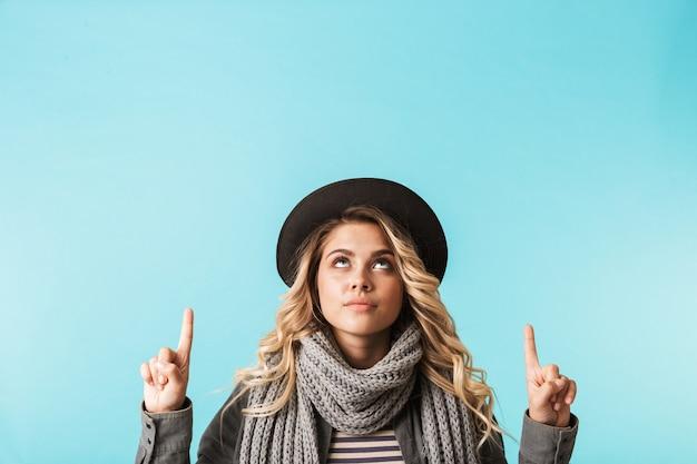 Cappello da portare della ragazza graziosa e una sciarpa che sta isolata sopra la parete blu, indicante lo spazio della copia